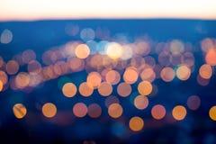 La ciudad se enciende por la tarde crepuscular con el fondo que empaña, cl Imagen de archivo