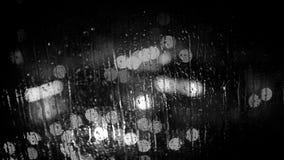 La ciudad se enciende según lo visto a través el vidrio de la ventana durante la lluvia Cantidad blanco y negro almacen de video