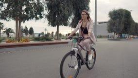 La ciudadana joven está montando la bici en ciudad en el día de verano, opinión sobre su cara almacen de video