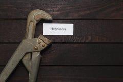 La clé à tube comprime un morceau de papier avec un bonheur d'inscription Photo stock