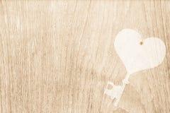La clé de coeur a embouti sur la texture en bois pour la valentine et épouser de retour Image libre de droits