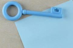 La clé en plastique bleue est placée sur la note de papier bleu Photographie stock libre de droits