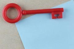 La clé en plastique rouge est placée sur la note de papier bleu Photo stock