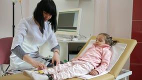 La clínica pediátrica, cardiograma para los niños, cardiólogo quita el cardiograma del corazón en hospital metrajes