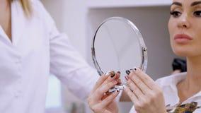 La clínica, sitio de la cosmetología, el doctor somete un espejo al paciente, discute el procedimiento del aumento del labio con metrajes