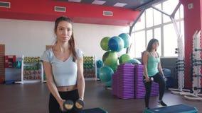 La clase de aeróbicos que caminaba junta llevó por el instructor y pesas de gimnasia de elevación en el gimnasio metrajes