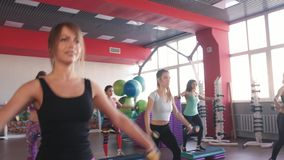 La clase de aeróbicos que caminaba junta llevó por el instructor y pesas de gimnasia de elevación en el gimnasio almacen de metraje de vídeo