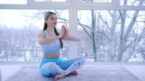 La clase de la yoga, mujer asombrosa respira profundamente durante la meditación en sitio cerca de ventana metrajes