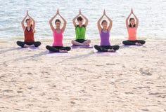 La classe de yoga à la plage de mer dans la soirée, groupe de personnes faisant des poses d'arbre avec la palourde détendent l'ém image libre de droits