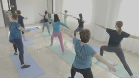 La classe de yoga faite de femmes âgées par milieu d'entreprise exerçant le guerrier posent dans un studio de forme physique en t clips vidéos