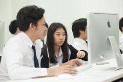 La classe A di studenti davanti ai loro schermi studia l'informatica Fotografie Stock