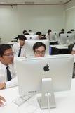 La classe A di studenti davanti ai loro schermi studia l'informatica Immagini Stock