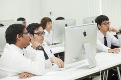 La classe A di studenti davanti ai loro schermi studia l'informatica Fotografia Stock Libera da Diritti