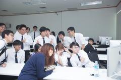 La classe A di studenti davanti ai loro schermi studia l'informatica Immagine Stock