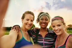 La classe diverse de yoga de trois femmes millénaires gaies prend un selfie au coucher du soleil en parc naturel Photo stock