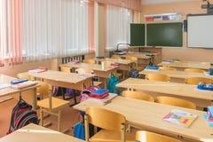 La classe intérieure dans l'école primaire, les bureaux d'étudiants et les professeurs de bureau embarquent à l'arrière-plan Photos stock