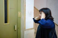 La claustrophobie affecte la femme mûre quand elle reste devant un ascenseur images libres de droits