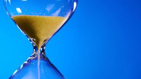 La clessidra giallo sabbia in una boccetta trasparente è sparsa su un fondo blu ed il tempo sta esaurendosi stock footage