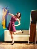 La cliente de femme tient des cintres avec des vêtements regardant dans le miroir photo stock