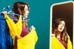La cliente de femme tient des cintres avec des vêtements regardant dans le miroir image stock
