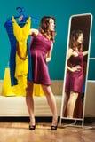 La cliente de femme tient des cintres avec des vêtements regardant dans le miroir images stock