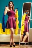 La cliente de femme tient des cintres avec des vêtements regardant dans le miroir photo libre de droits