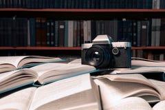 La cámara vieja de la foto está en muchos libros abiertos llenados para arriba con muchos reserva Imagenes de archivo