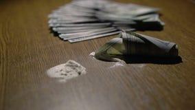 La cocaina ha sniffato su uno specchio attraverso una banconota rotolata di 100 dollari, 4k stock footage