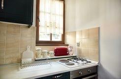 La cocina en el apartamento Estufa de gas, tostadora, tarros del condimento imagen de archivo libre de regalías