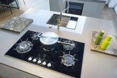 La cocina, moderno blanco de los gabinetes kichen con la gama de la isla imágenes de archivo libres de regalías