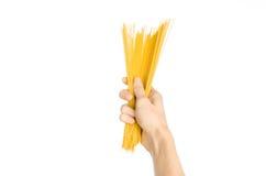 La cocina y el tema de cocinar: la mano del hombre que sostiene una pila de espaguetis crudos en un fondo blanco aislado en estud Foto de archivo libre de regalías