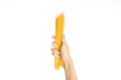 La cocina y el tema de cocinar: la mano del hombre que sostiene una pila de espaguetis crudos en un fondo blanco aislado en estud Imágenes de archivo libres de regalías