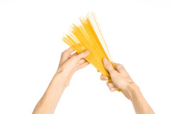 La cocina y el tema de cocinar: la mano del hombre que sostiene una pila de espaguetis crudos en un fondo blanco aislado en estud Foto de archivo