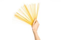 La cocina y el tema de cocinar: la mano del hombre que sostiene una pila de espaguetis crudos en un fondo blanco aislado en estud Fotos de archivo libres de regalías