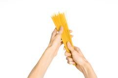 La cocina y el tema de cocinar: la mano del hombre que sostiene una pila de espaguetis crudos en un fondo blanco aislado en estud Imagenes de archivo