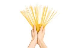 La cocina y el tema de cocinar: la mano del hombre que sostiene una pila de espaguetis crudos en un fondo blanco aislado en estud Fotografía de archivo libre de regalías