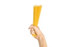 La cocina y el tema de cocinar: la mano del hombre que sostiene una pila de espaguetis crudos en un fondo blanco aislado en estud Imagen de archivo libre de regalías