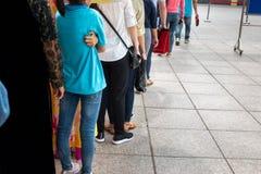 La coda della gente asiatica aspetta nella linea in via urbana fotografie stock libere da diritti