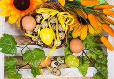 La codorniz y el pollo eggs en una cesta con la flor de la primavera Imagen de archivo libre de regalías