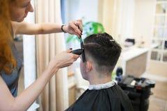 La coiffeuse de fille avec les cheveux rouges bouclés coupe le jeune, beau type dans un salon de beauté photographie stock libre de droits