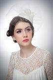 La coiffure et composent - le beau portrait d'art de jeune fille Brune mignonne avec le chapeau et le voile blancs, tir de studio Photo libre de droits