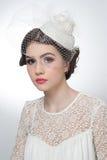 La coiffure et composent - le beau portrait d'art de jeune fille Brune mignonne avec le chapeau et le voile blancs, tir de studio Photos libres de droits