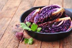 La col roja coció en aceite de oliva con las escamas de la pimienta de chile y la sal del mar Comida vegetariana se teñe la image Imagen de archivo