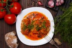 La col rueda en salsa del tomate en una placa blanca Fotos de archivo