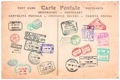 La colección de pasaporte sella en una postal del vintage Foto de archivo
