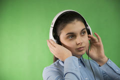 La colegiala adolescente escucha música en auriculares Foto de archivo