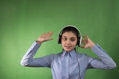 La colegiala adolescente escucha música en auriculares Fotografía de archivo