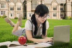 La colegiala asiática utiliza el ordenador portátil en el campo Imagen de archivo libre de regalías