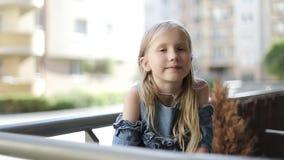 La colegiala atractiva se sienta en el balcón en el verano almacen de metraje de vídeo