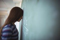 La colegiala cansada que se coloca con los ojos cerrados acerca a la pizarra en sala de clase Imagen de archivo libre de regalías